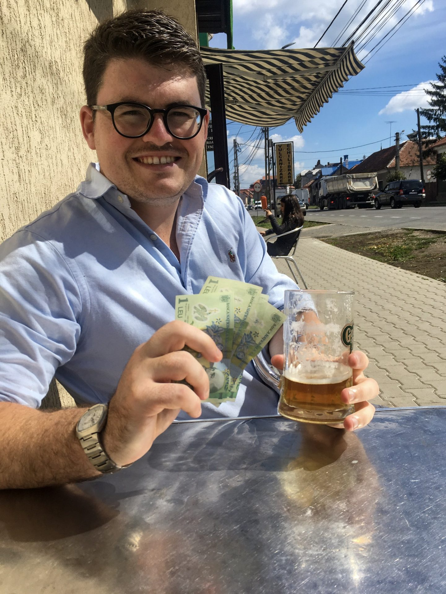 Man holding beer and cash to demonstrate how cheap beer is in Eastern Europe