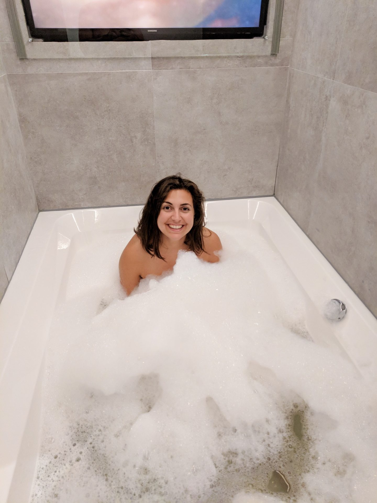 Girl in double width bubble bath with tv in the wall behind - cheap city breaks