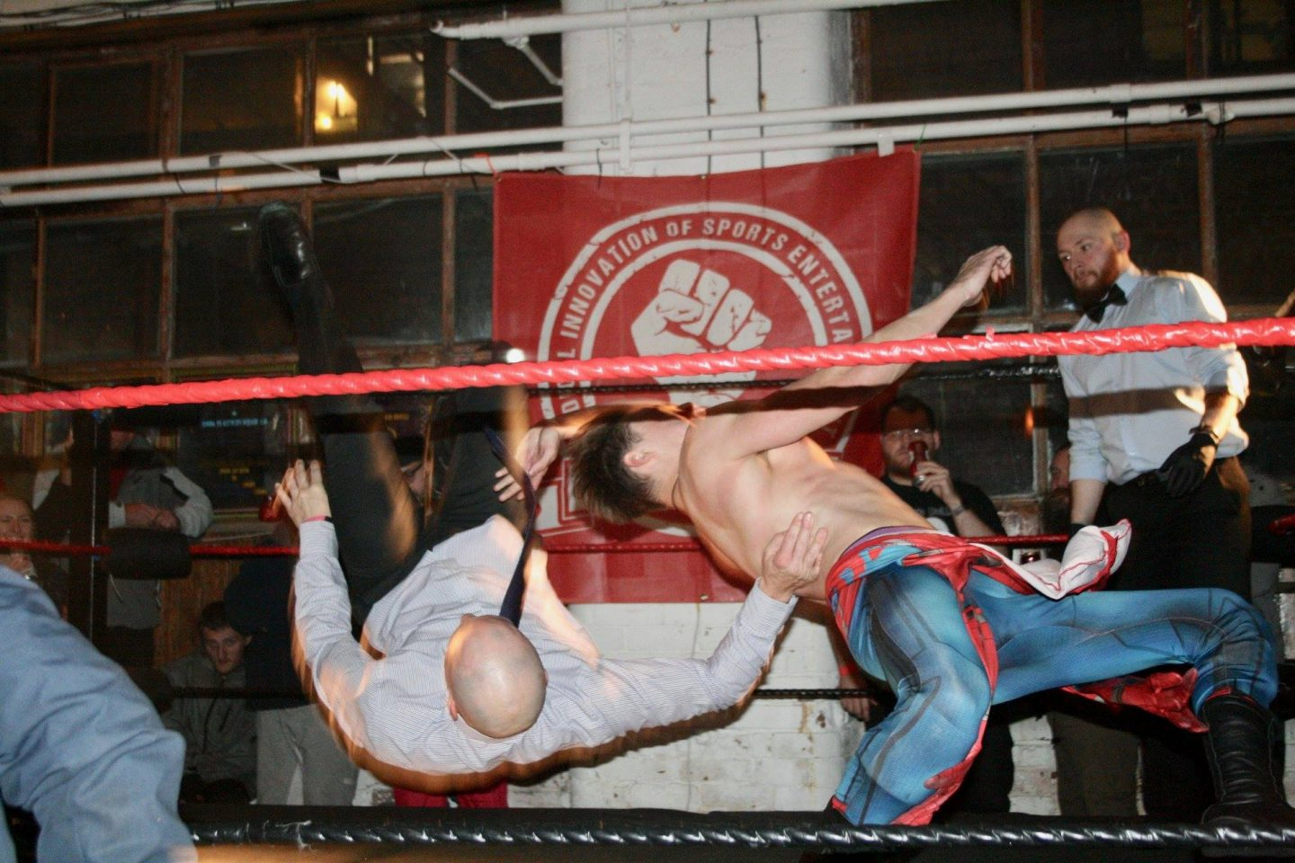 Spiderman wrestling a man in a suit and tie - action shot of them both in the air
