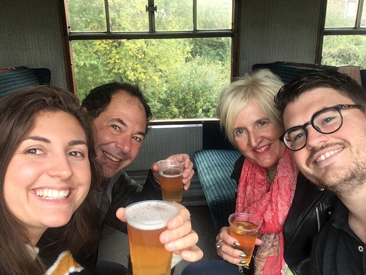 Four people enjoying a beer aboard the steam train at the KWVR beer festival