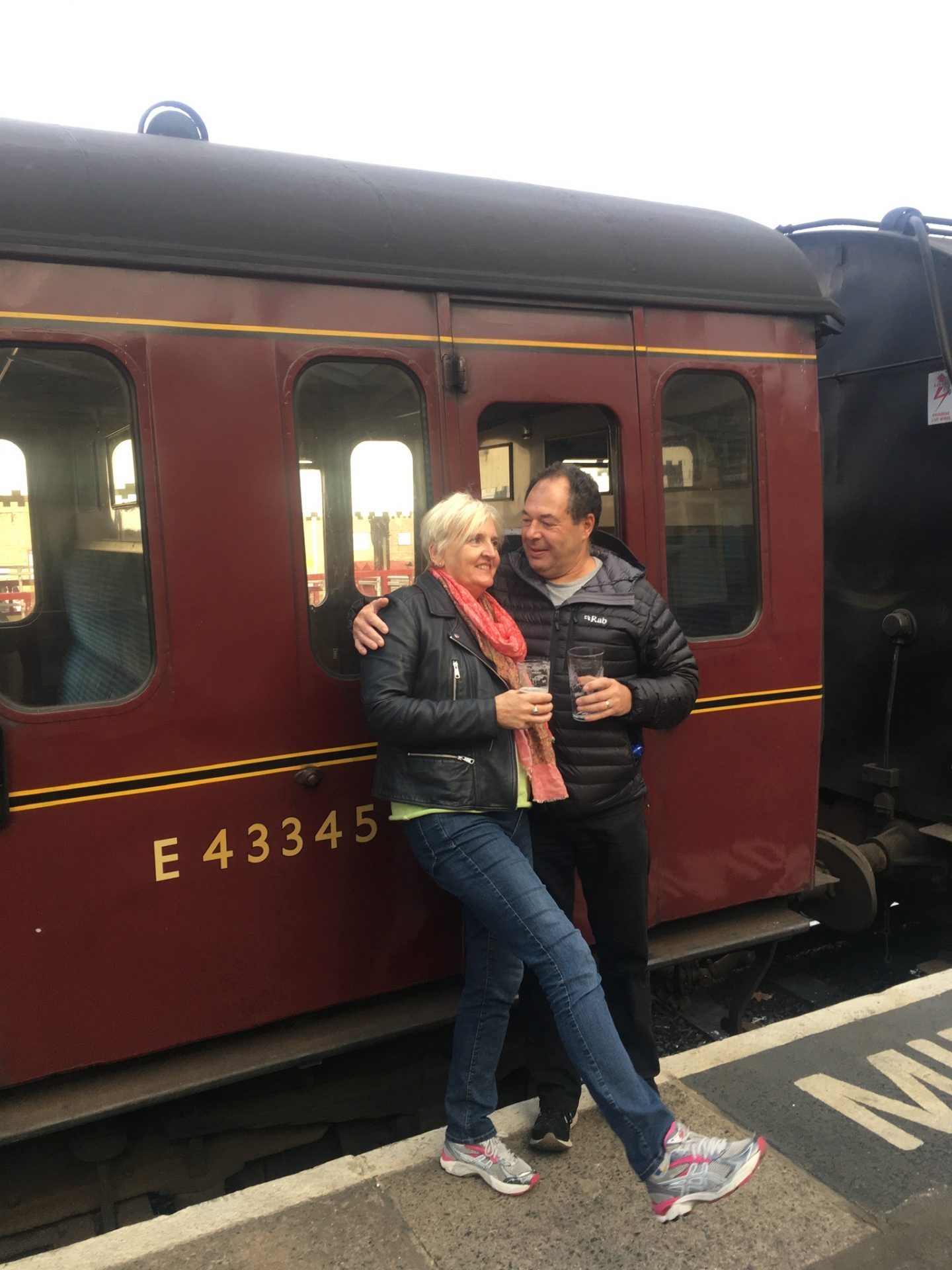 Two people in their fifties stood next to a steam train with a beer in hand at the KWVR beer festival