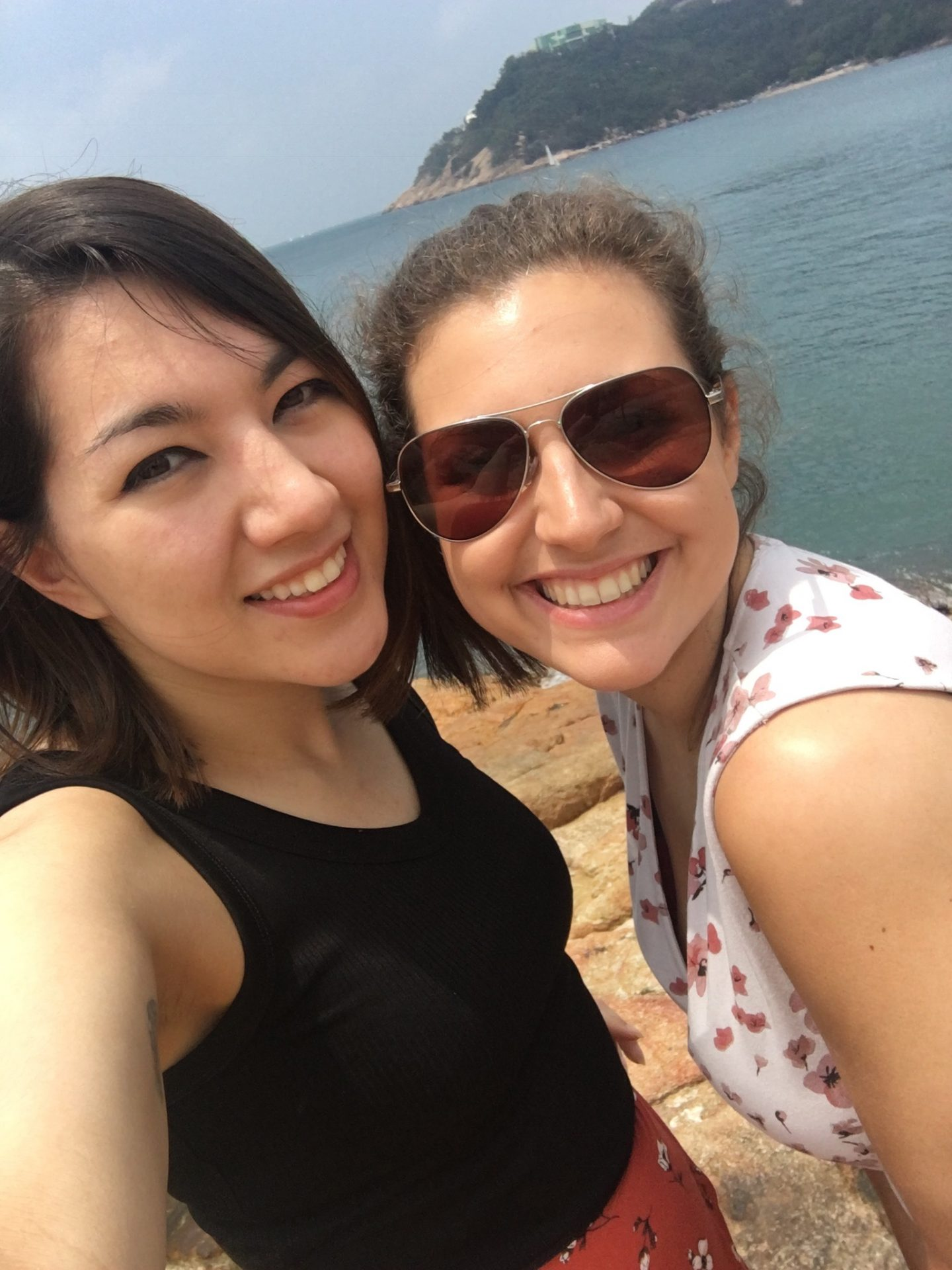 Two girls in Stanley in Hong Kong on a sunny day, looking directly into the camera smiling with the sea behind
