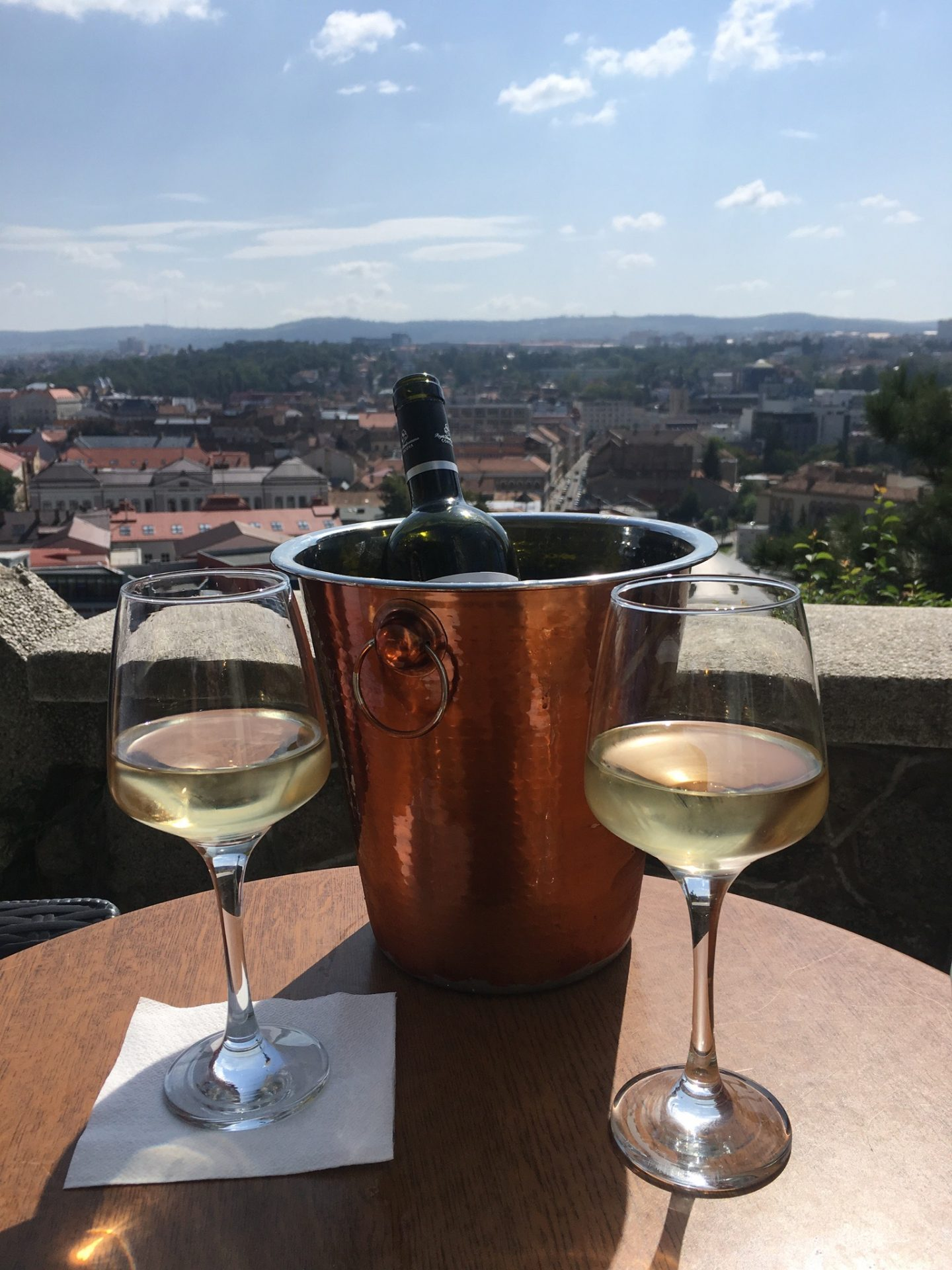 cluj napoca things to do: bottle of wine and two glasses overlooking the city from centurian hill