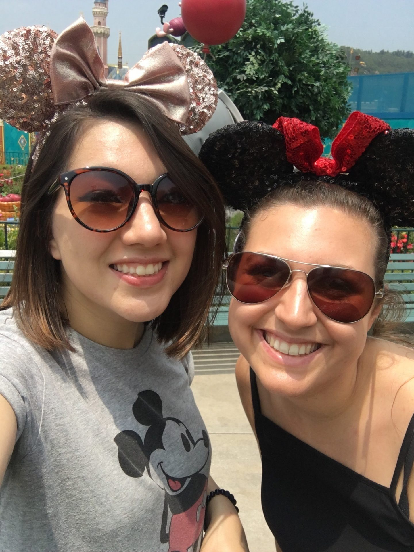 Two girls at Disneyland in Hong Kong wearing minnie mouse ears and looking directly at the camera