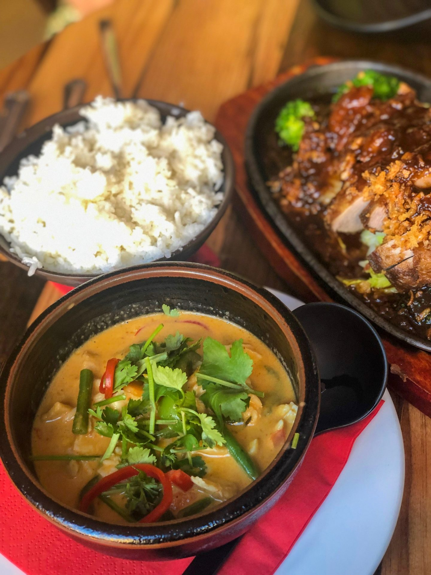 An overhead shot at a thai restaurant in Leeds, with a full bowl of thai curry in shot and part of two other dishes in shot