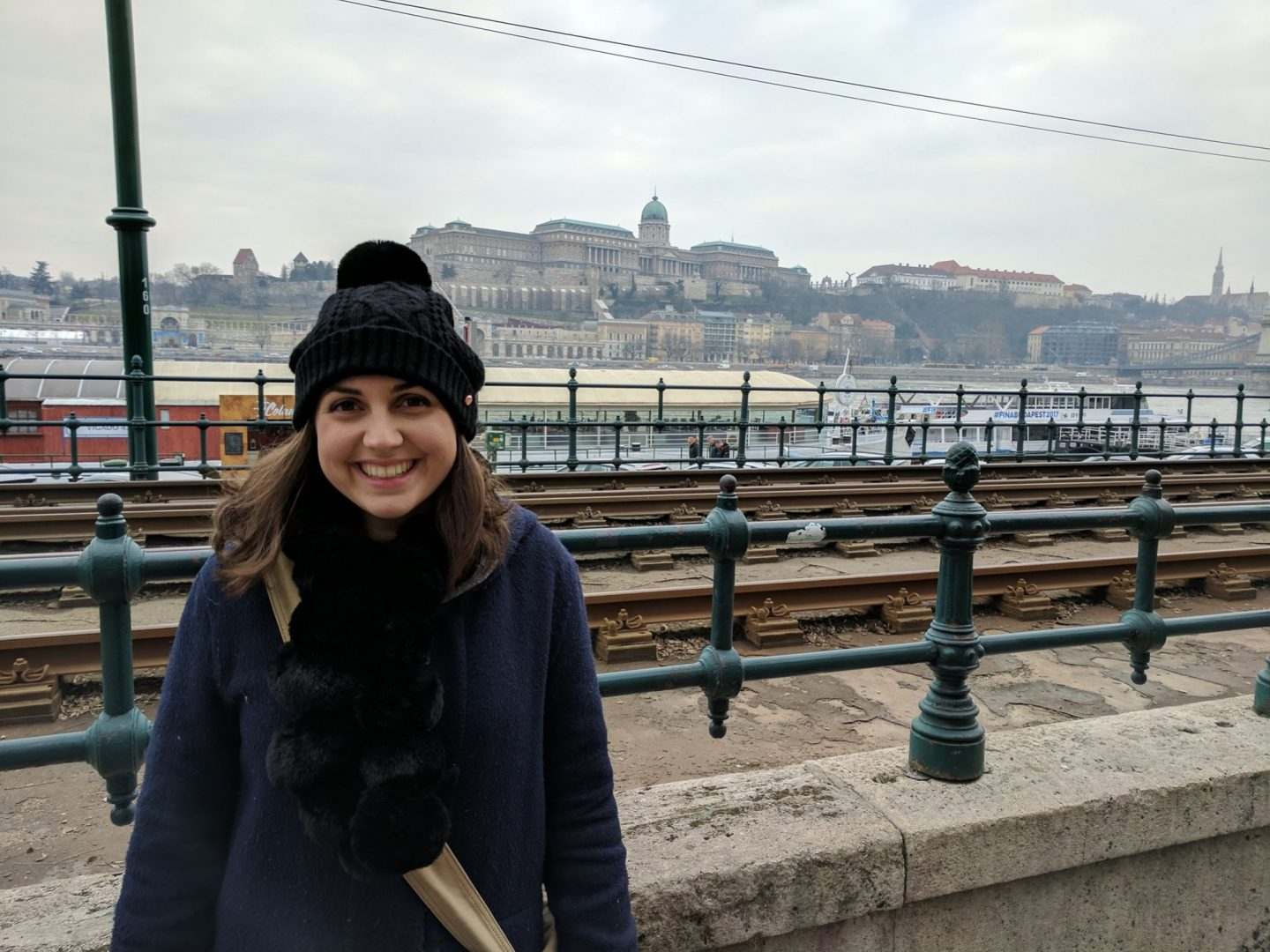 things to do in Budapest: girl wearing a black bobble hat looking directly into the camera and smiling, with Budapest landscape in the background