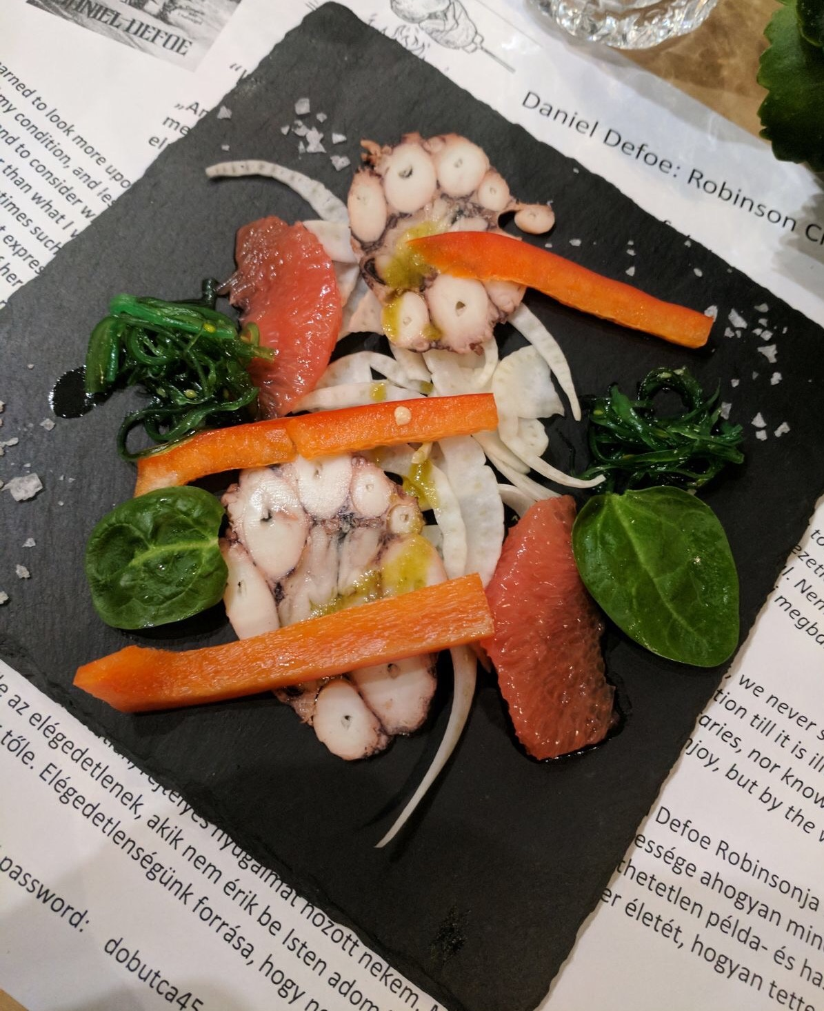 restaurants in budapest: a plate of octopus carpaccio with grapefruit eaten at Konvy Bar