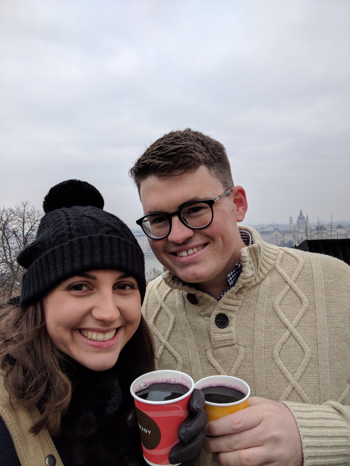 A couple smiling at the camera and holding a cup of hot mulled wine - things to do in Budapest