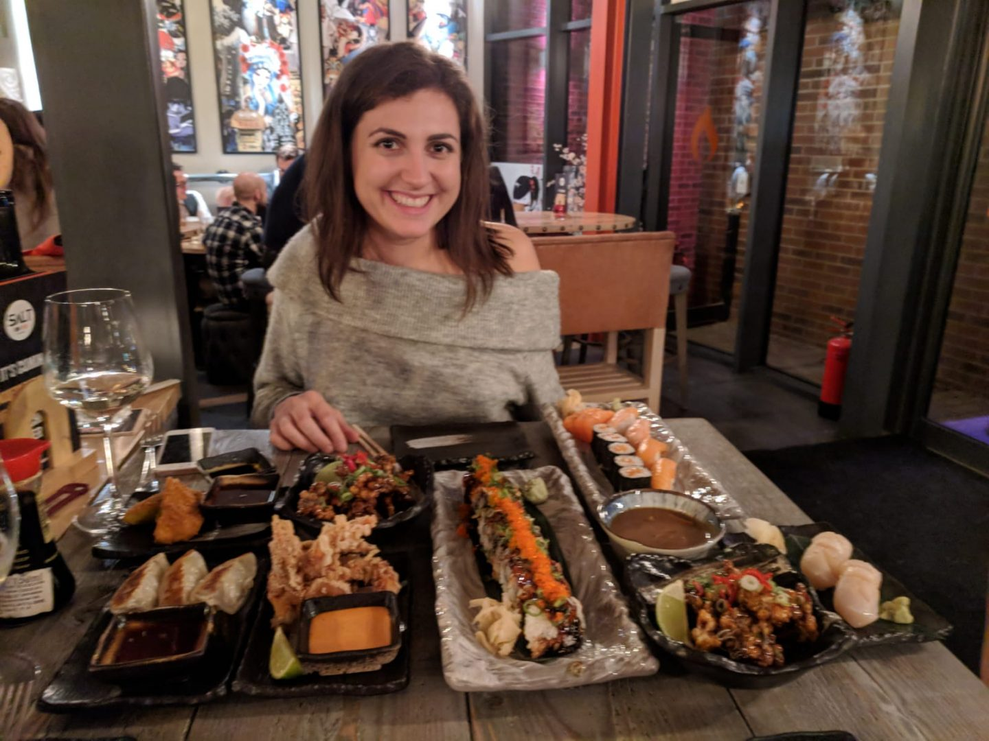Leeds sushi: girl with a table full of sushi dishes in front of her, smiling into the camera