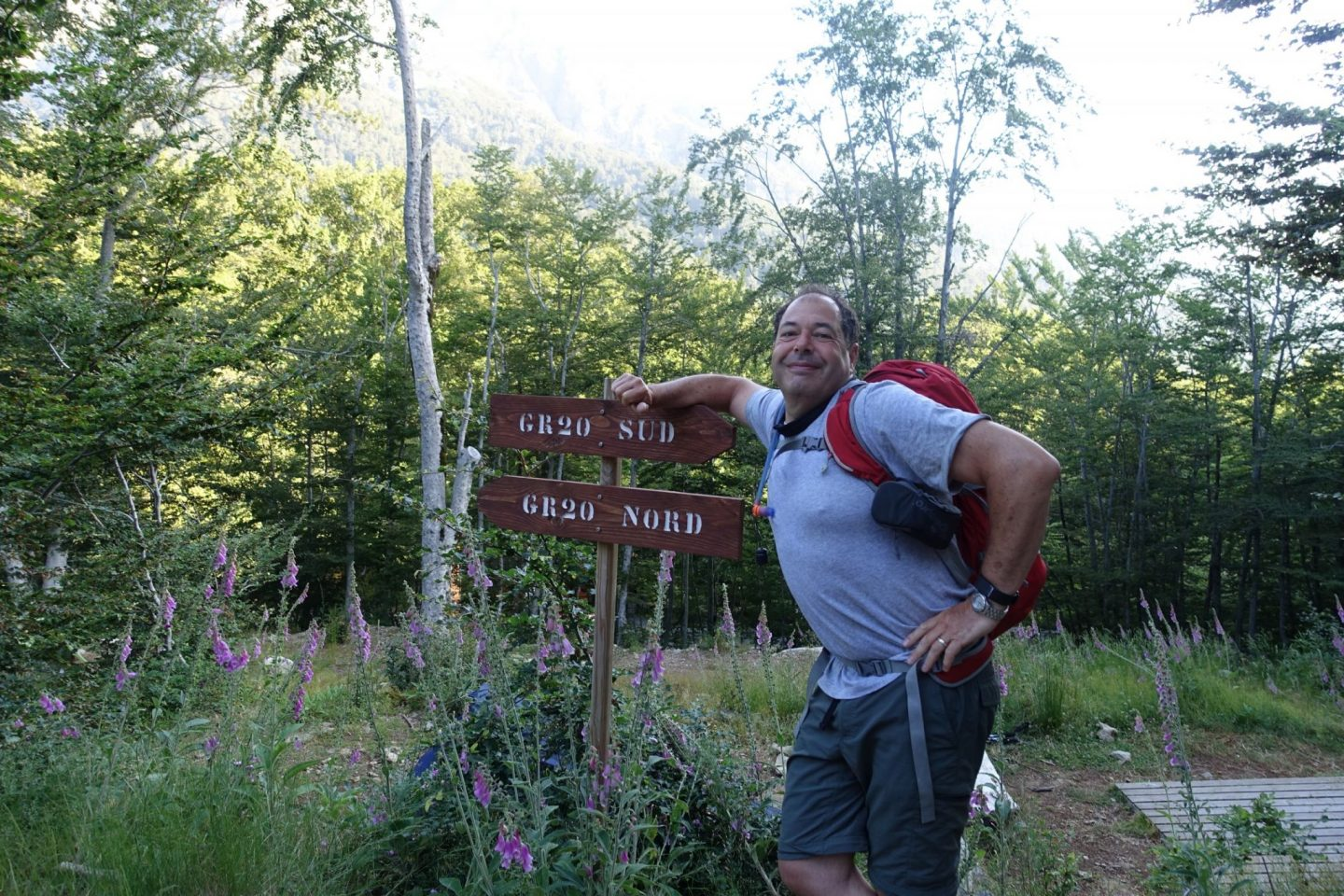 Halfway point on the GR20: main smiling and leaning against a wooden sign pointing north and south