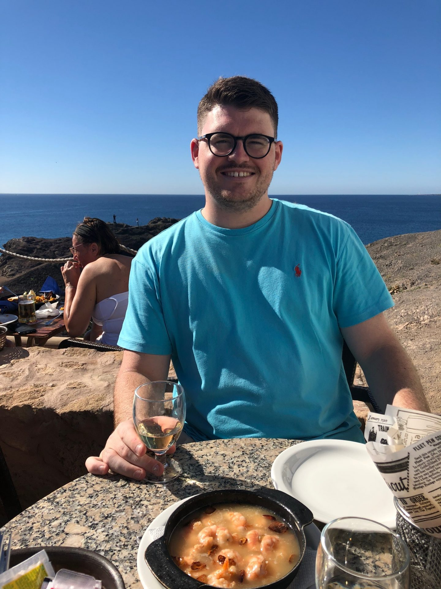 Man with glass of wine and garlic prawns, blue sky behind and smiling directly at the camera
