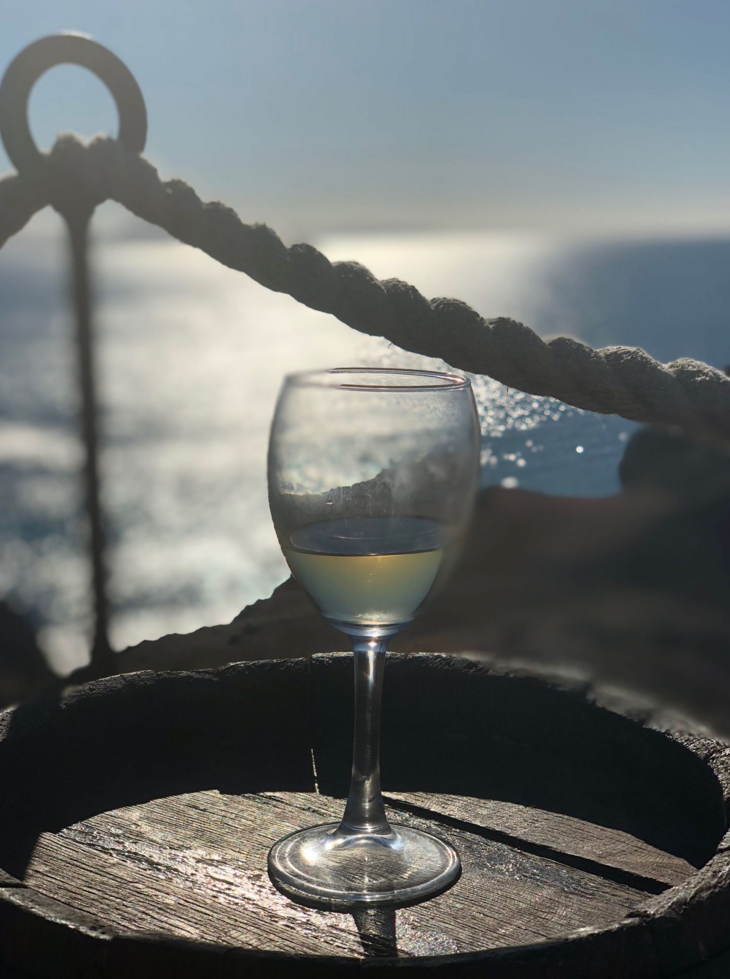 A Glass of white wine perched on a barrel with the sea and evening sun behind, one of the best restaurants in playa blanca
