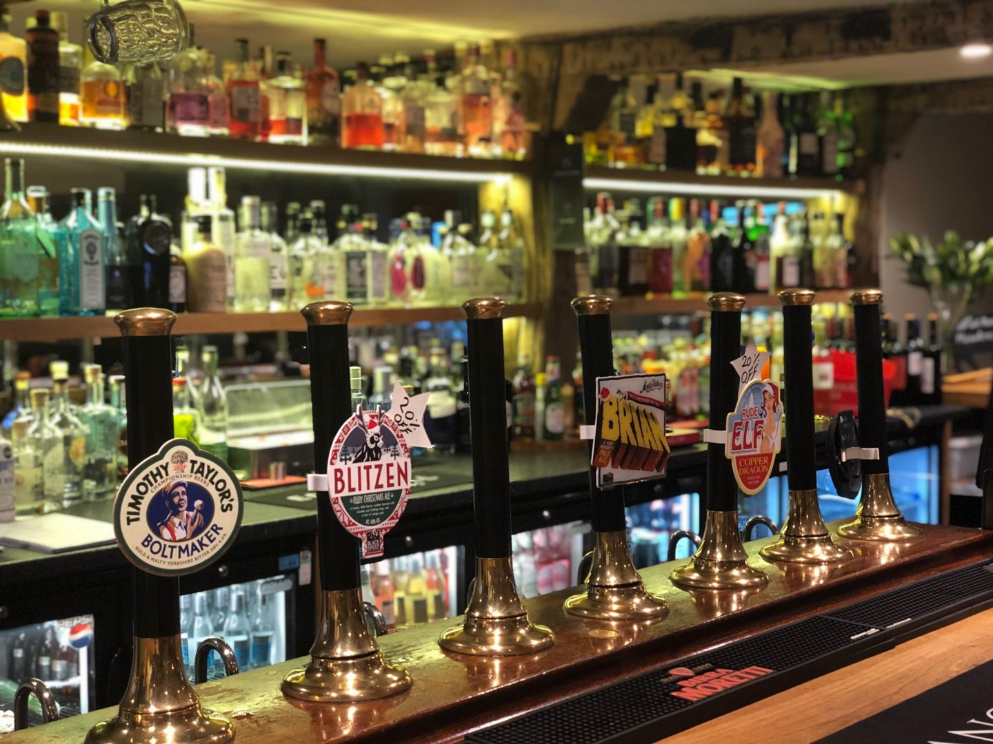 Marton Arms Bar near White Scar Cave, showing a bar of hand pulls and an extensive gin selection just out of focus
