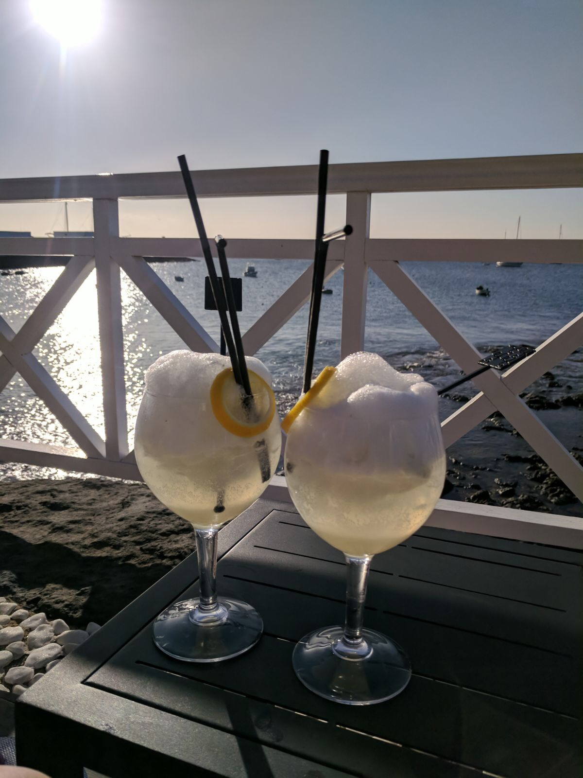 El Mirador, one of the best restaurants in Playa Blanca. Two glasses of gin fizz with views of the harbour in the background.