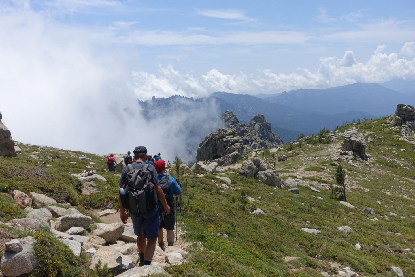 GR20, group walking down path with a cloud in front of them, grass to the side and rocky terrain ahead