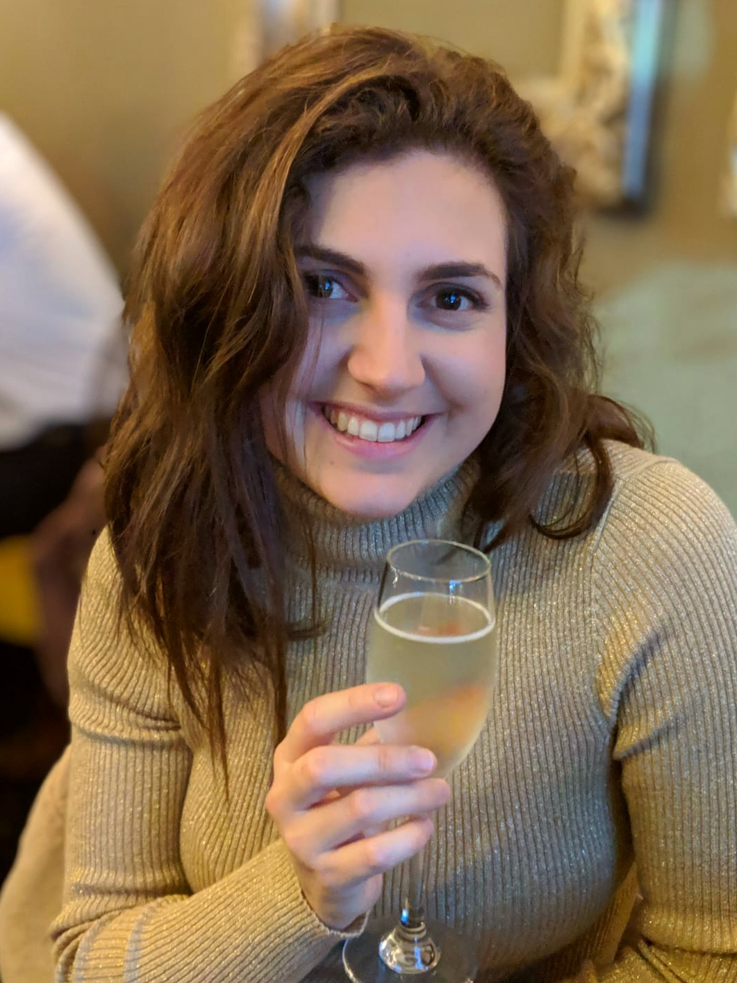 Nell holding a glass of champagne at Australasia, one of the manchester restaurants, and smiling at the camera