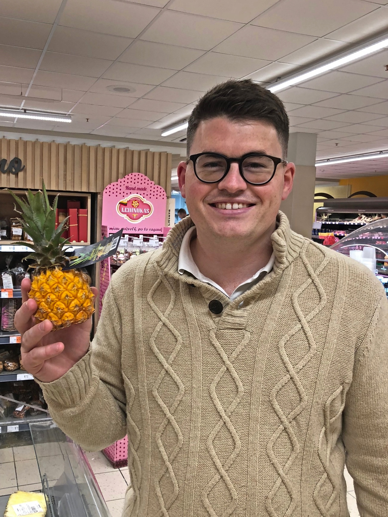 Billy in a supermarket in Vilnius holding a tiny pineapple and laughing