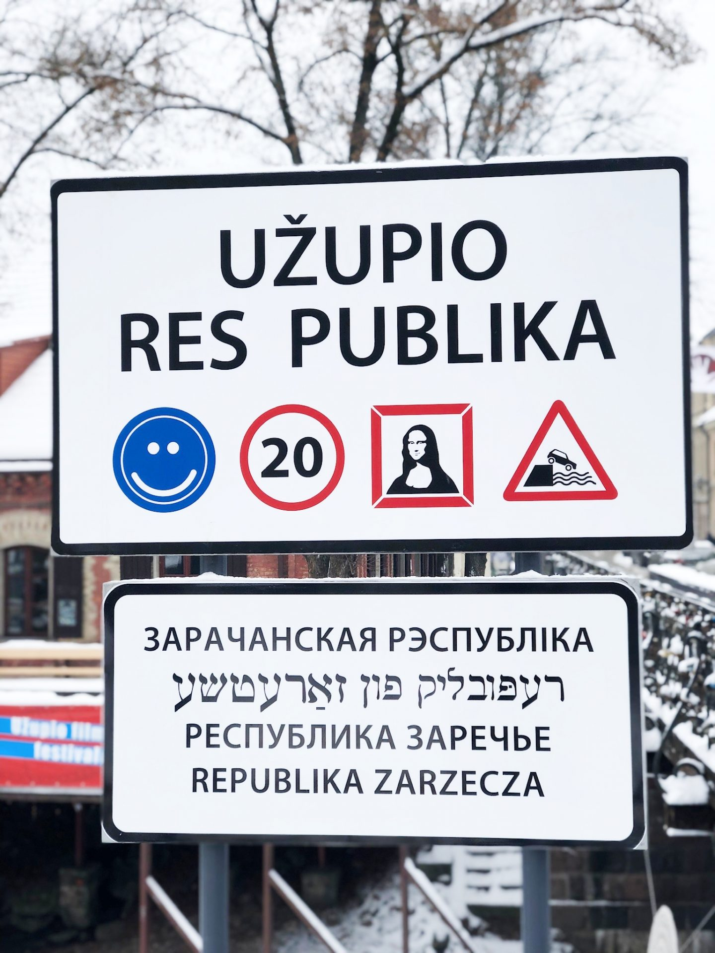 A sign showing Uzupio Res Publica with icons below it featuring a smiley face, a 20 miles per hour warning an a picture of the mona lisa.