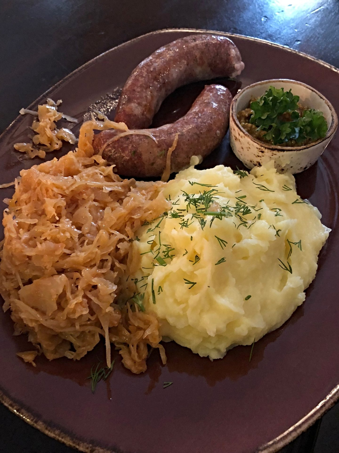 Best restaurants in Vilnius: sausage, mash and Sauerkraut on a brown plate, huge portions! Where to eat in Vilnius and Trakai