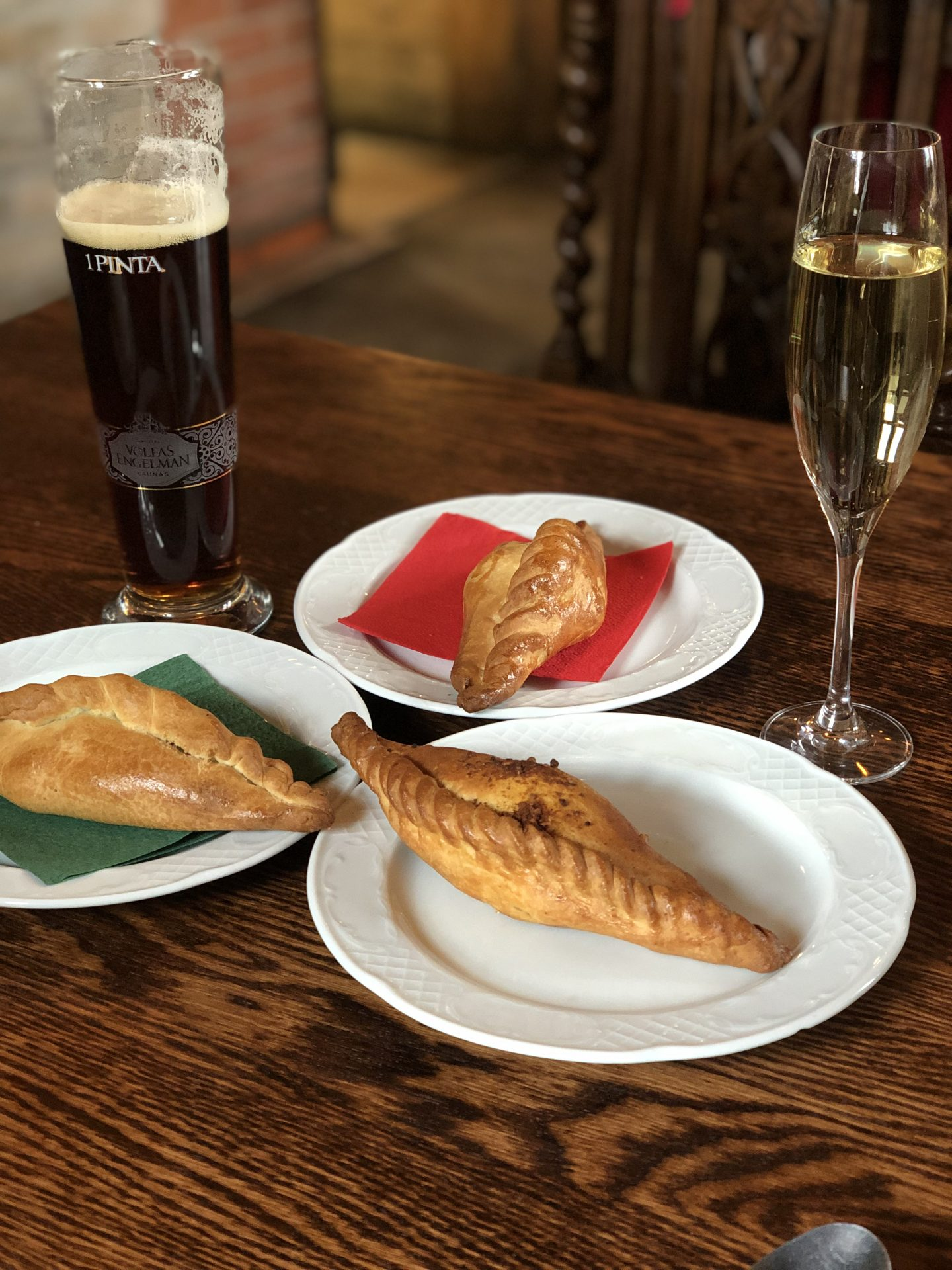 best restaurants in Vilnius: Kibinine at Senoji Kibininė, on three white plates with a glass of sparkling wine and a beer next to them