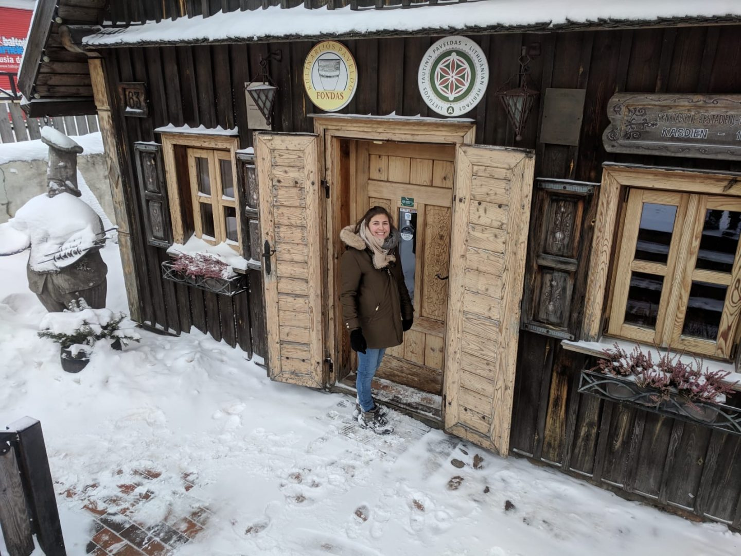 best restaurants in vilnius: Nell stood outside Senoji Kibininė in Trakai. She's stood next to a large wooden door, and snow is on the ground.