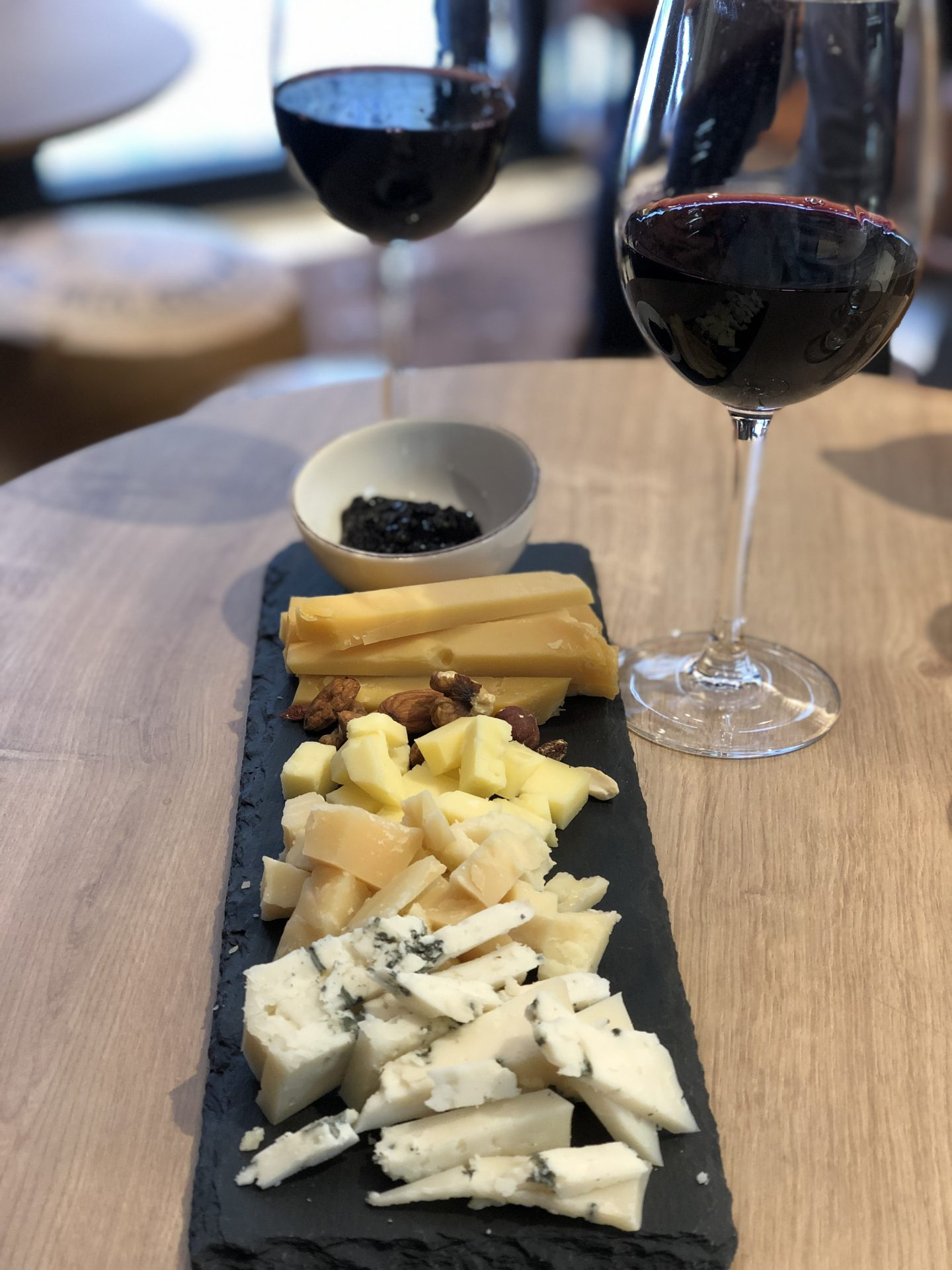 Best restaurants in Vilnius: Cheese board with three huge piles of cheese on a slate, with two glasses of red wine at the end of the board