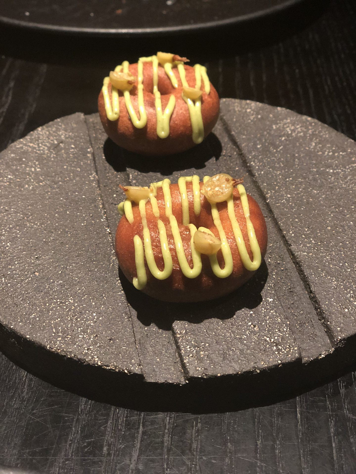 best restaurants in Vilnius: Džiaugsmas duck dougnuts, a warm orange colour with bright yellow sauce on top, served on a round slate plate.