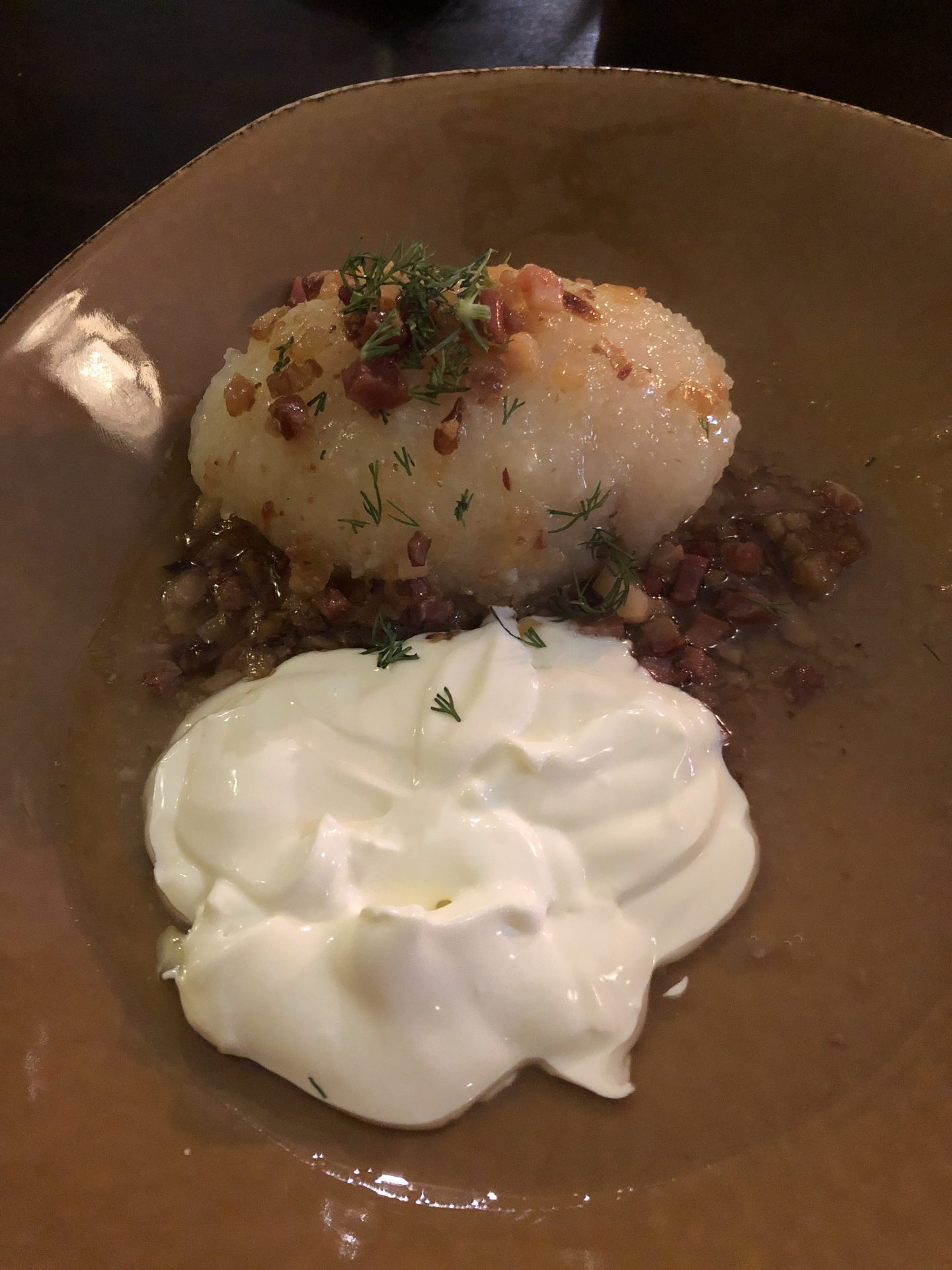 best restaurants: Cepelinai eaten in Vilnius. Image shows a large dumpling glistening with fat and covered in bacon lardons, with a side of soured cream.