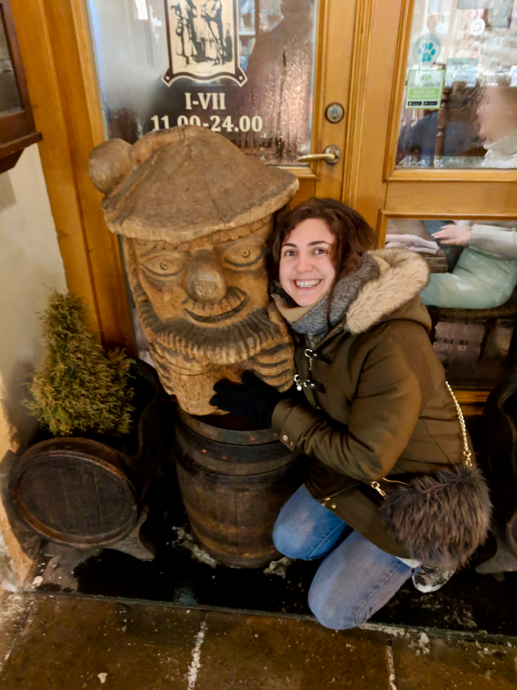 Best Restaurants in Vilnius: Nell, with slightly red wine stained teeth, crouching down next to a wooden statue of a face balanced on top of a beer barrel and smiling.