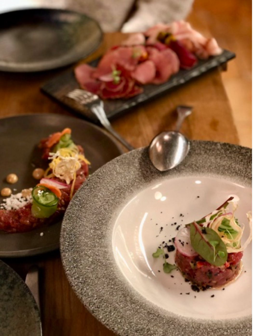best restaurants in Vilnius: three small plates at Somm in Vilnius, all served one different plates and with a fork and spoon balanced on the edge of the plates