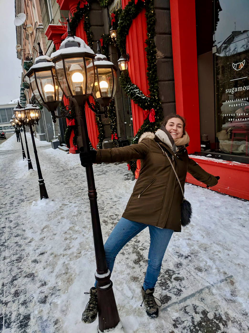 Best restaurants in Vilnius: Nell outside Sugamour, swinging around a lamp post and smiling at the camera, surrounded by snow.