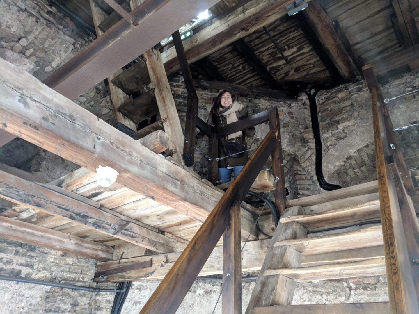 things to do in Vilnius in winter: Nell climbing the cathedral bell tower in Vilnius. She's looking down from half way up some wooden steps with a huge grin on her face