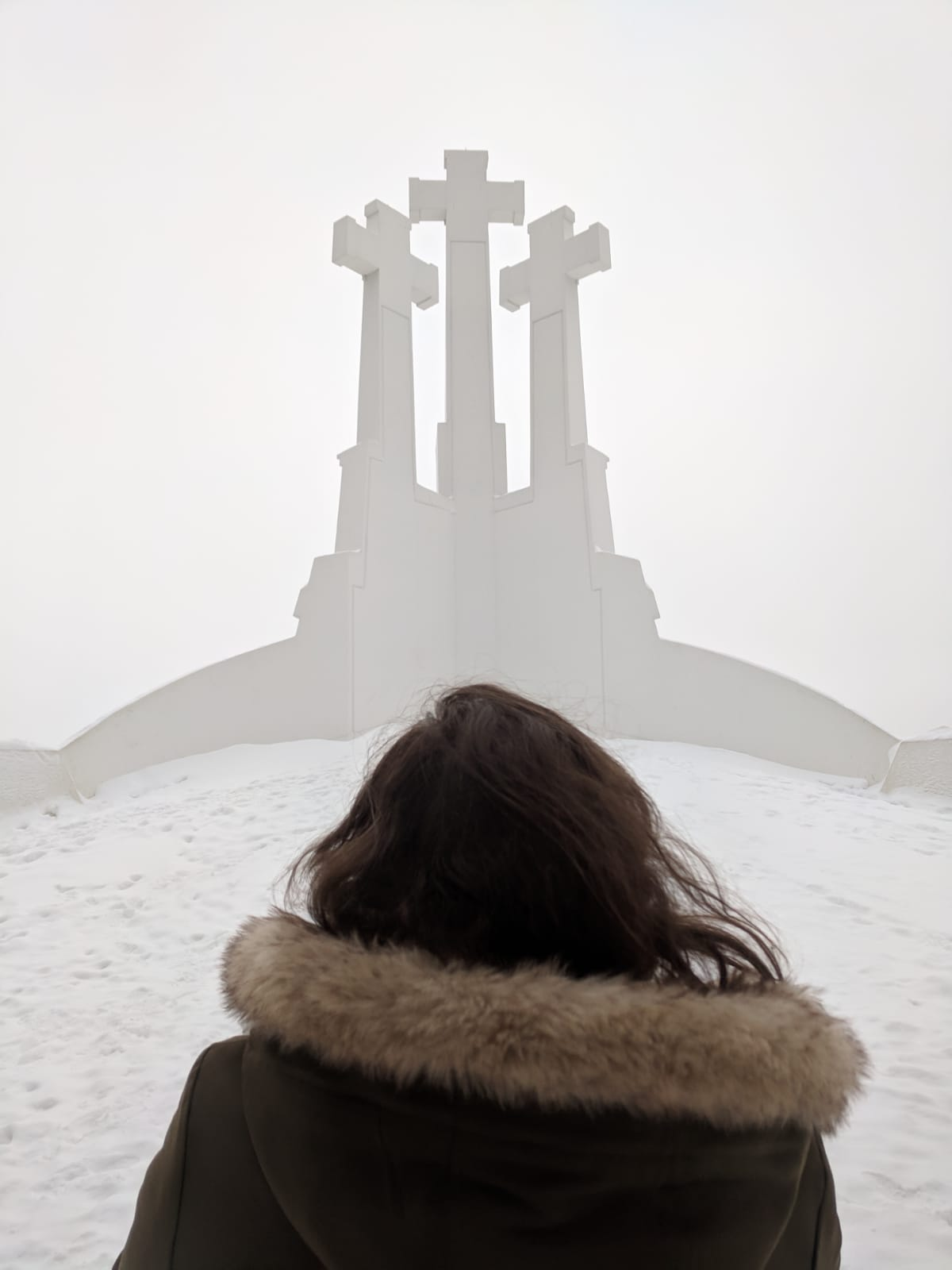things to do in Vilnius in winter: Nell staring up at the three crosses at the top of the hill of three crosse