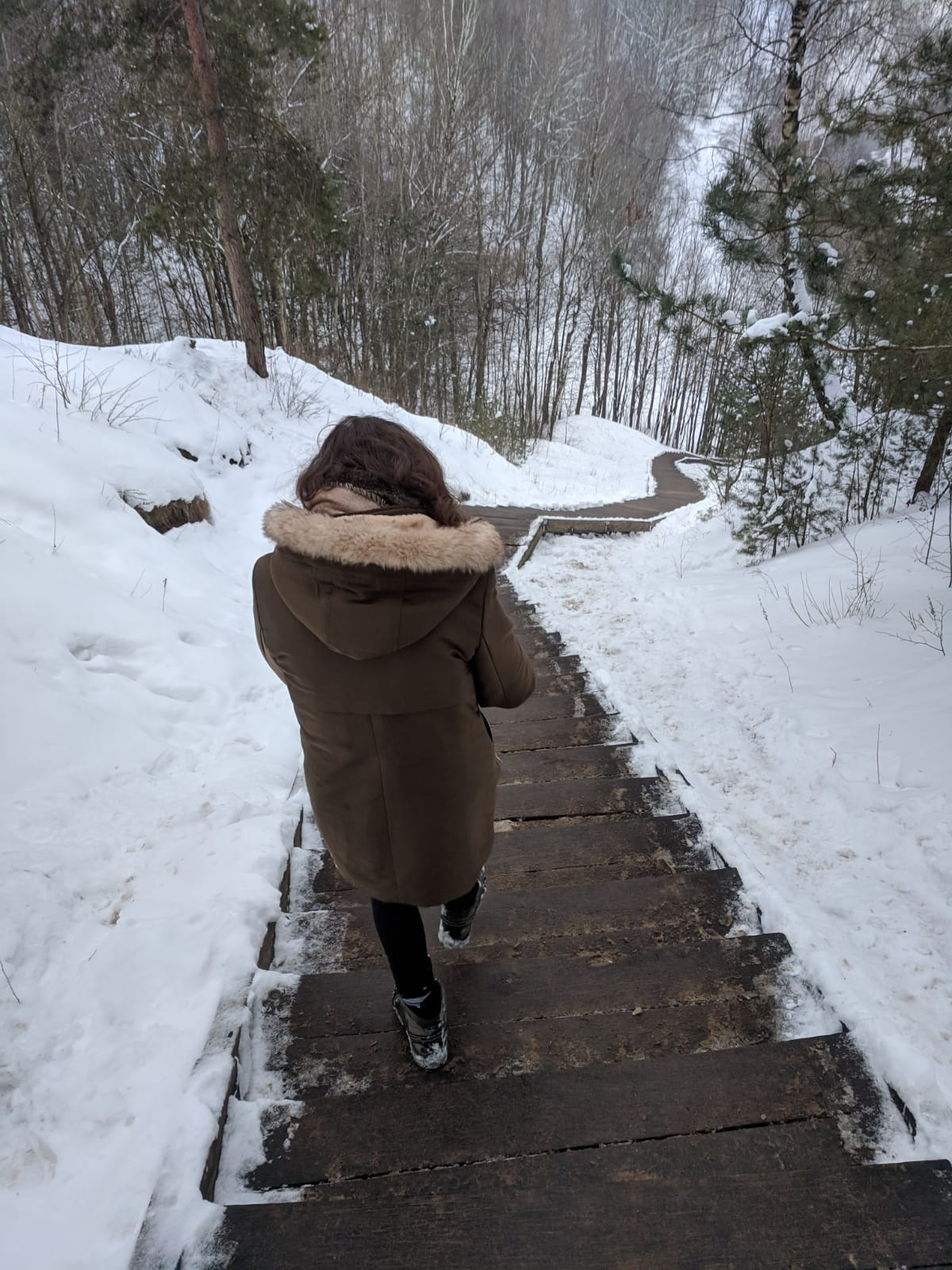 things to do in Vilnius in winter: Nell walking down never-ending wooden steps after visiting the hill of three crosses