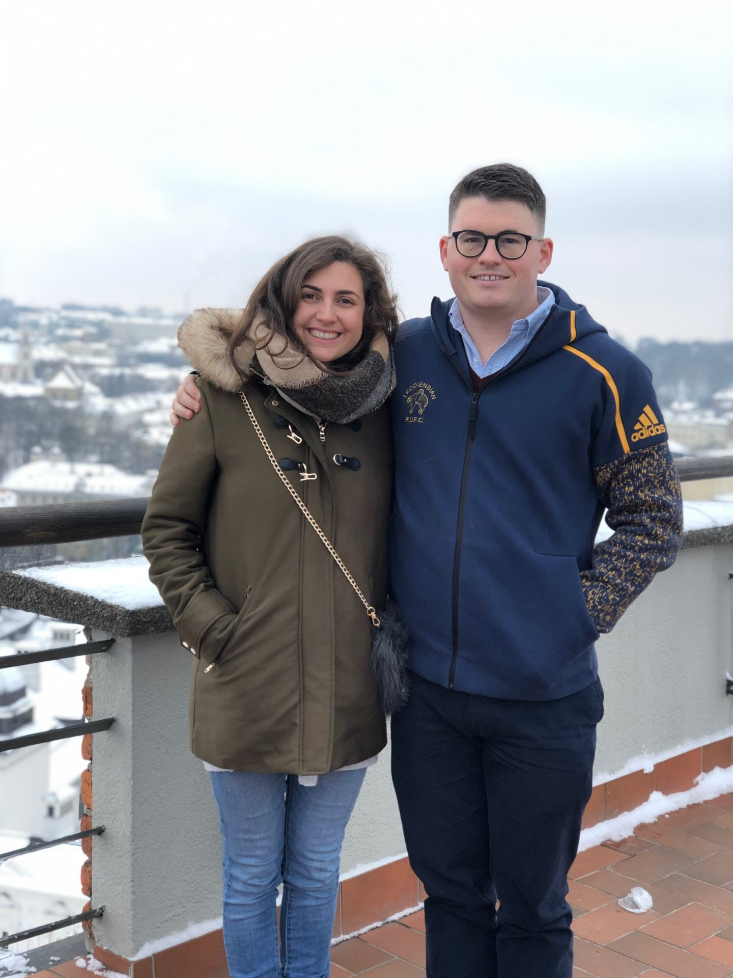 things to do in vilnius in winter: Nell and Billy stood on the observation deck of Gediminas' Tower, looking at the camera and smiling.