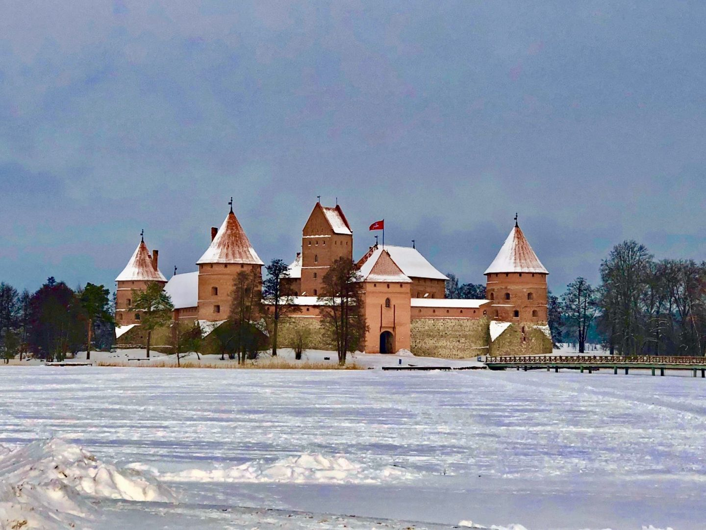 things to do in Vilnius in winter: Trakai castle surrounded by snow, with a moody grey sky behind