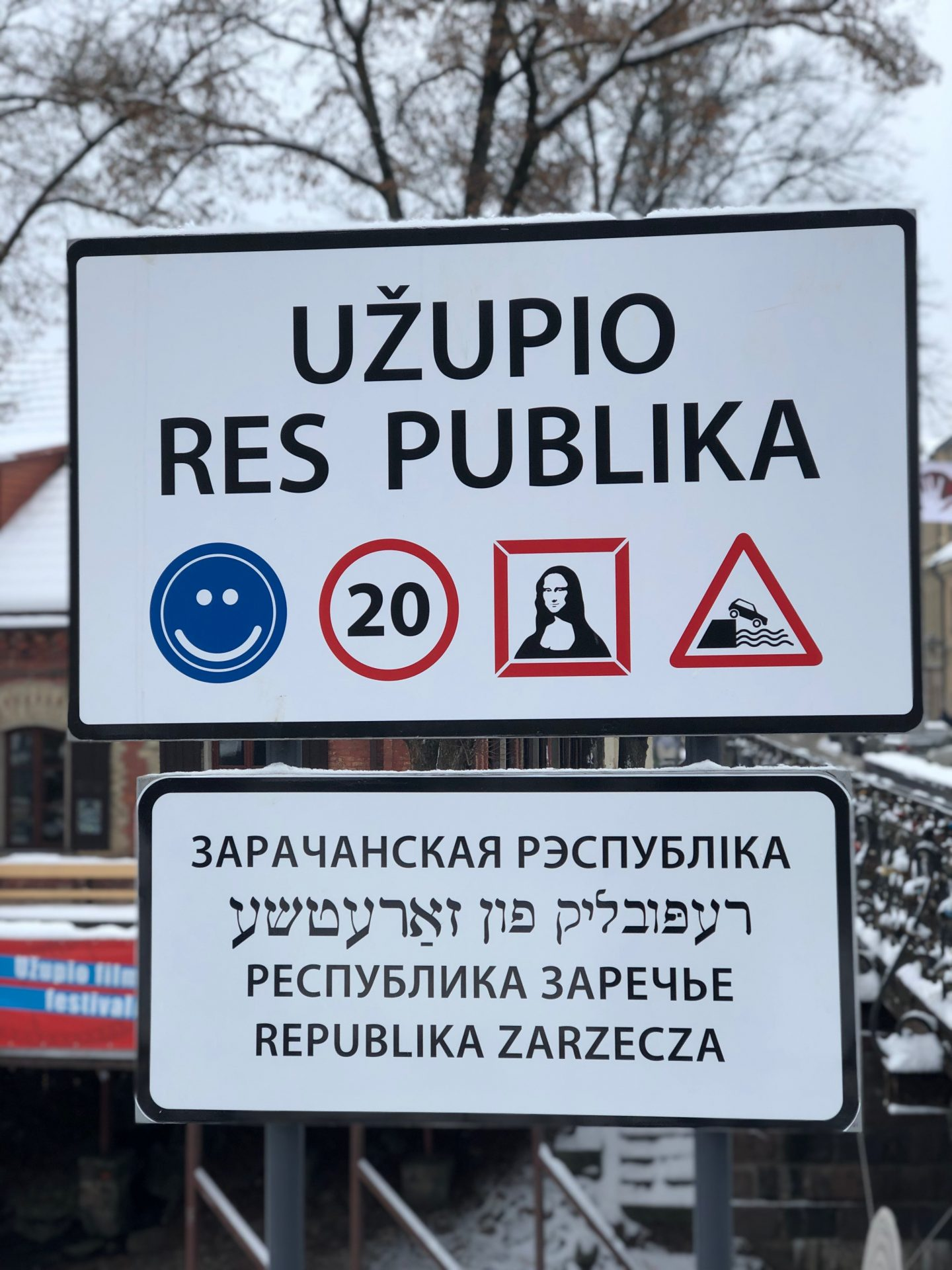 Things to do in Vilnius in winter: A sign showing Uzupio Res Publica with icons below it featuring a smiley face, a 20 miles per hour warning an a picture of the mona lisa.