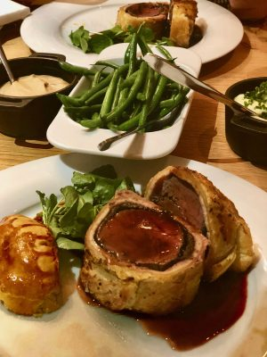 black swan helmsley hotel:  white round plate contains two thich slices of beef wellington with a rich gravy poured over the top. Behind that is a dish of green beans, of mash and of celeriac puree, each with a spoon.