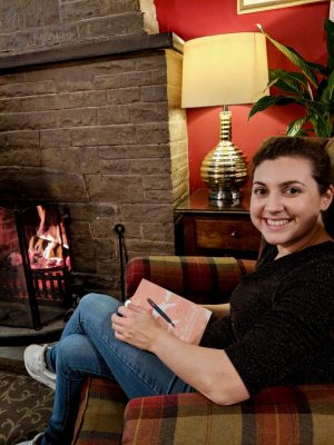 black swan helmsley hotel: Nell sat in a chequered armchair next to a log fire, holding a book in her lap and smiling at the camera