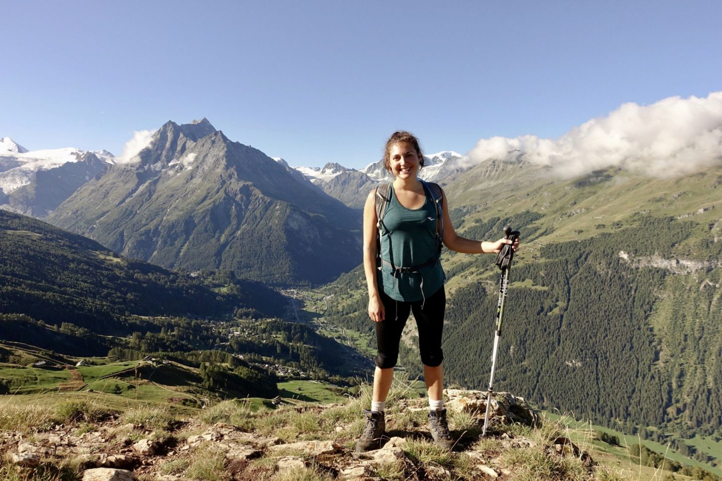 Nell hiking with a stunning mountain and valley in the background, showing off her boots and hiking poles as her hiking essentials