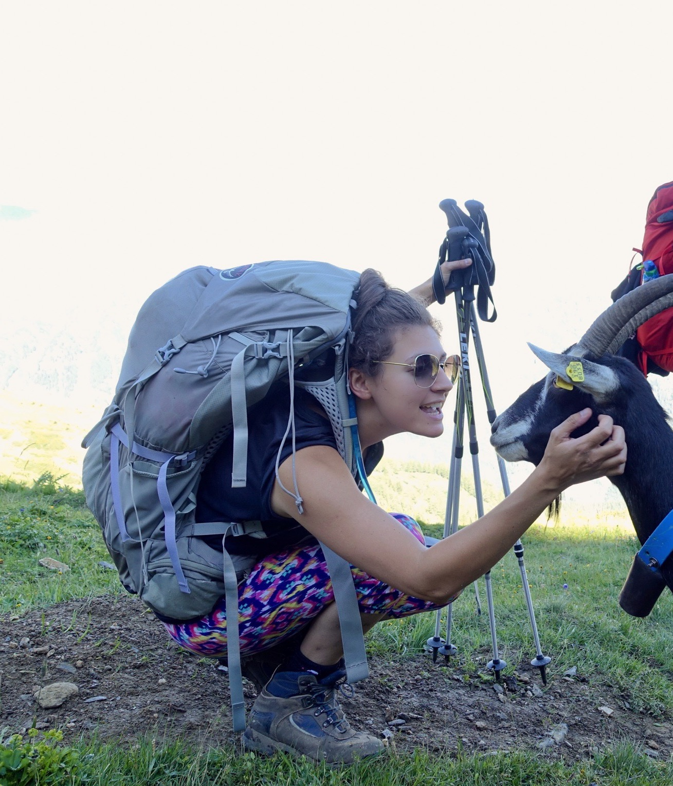 Nell crouching down to stroke a goat whilst hiking. In the image is her backpack and hiking poles, which she describes as her hiking essentials