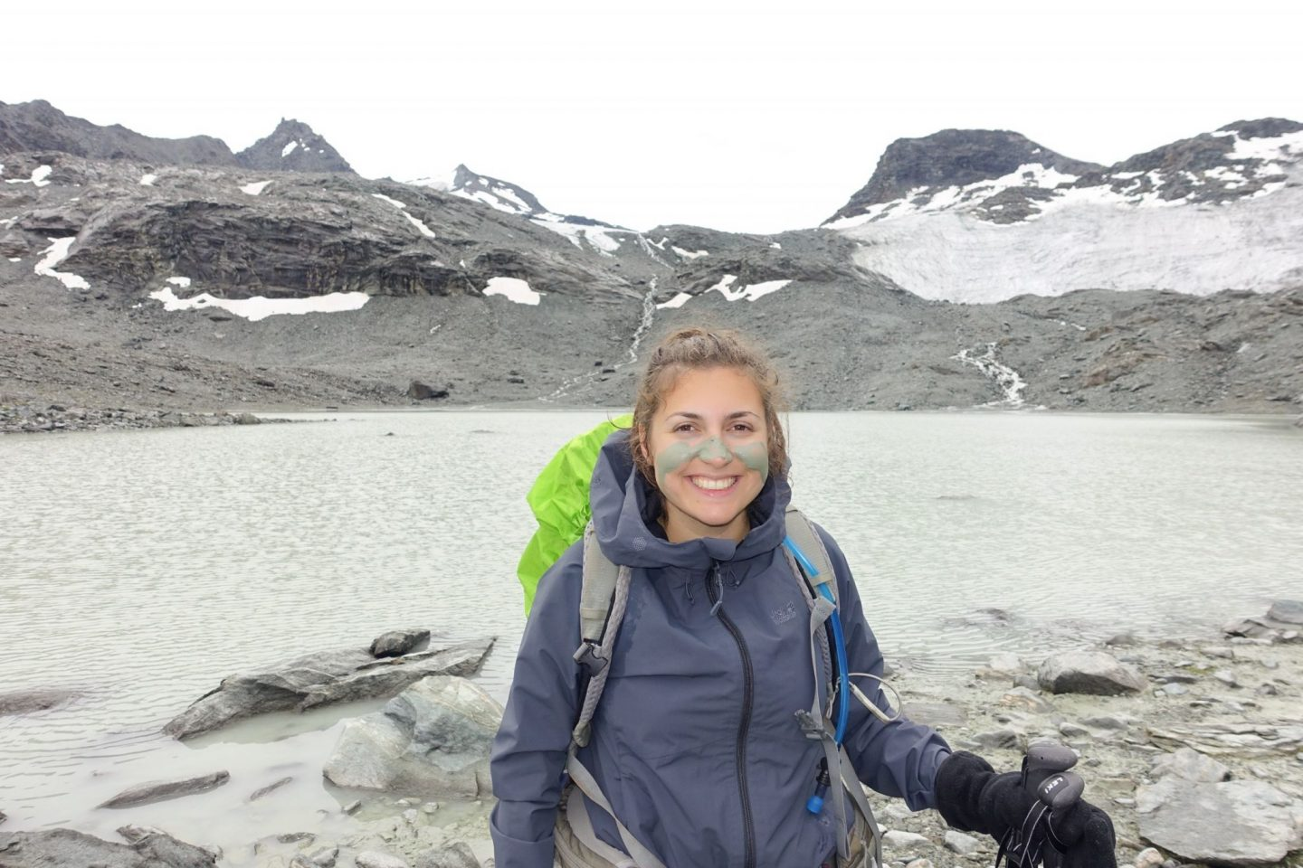 Nell smiling at the camera with a lake in the background, and clay streaks on her face. She's wearing waterproof hiking essentials