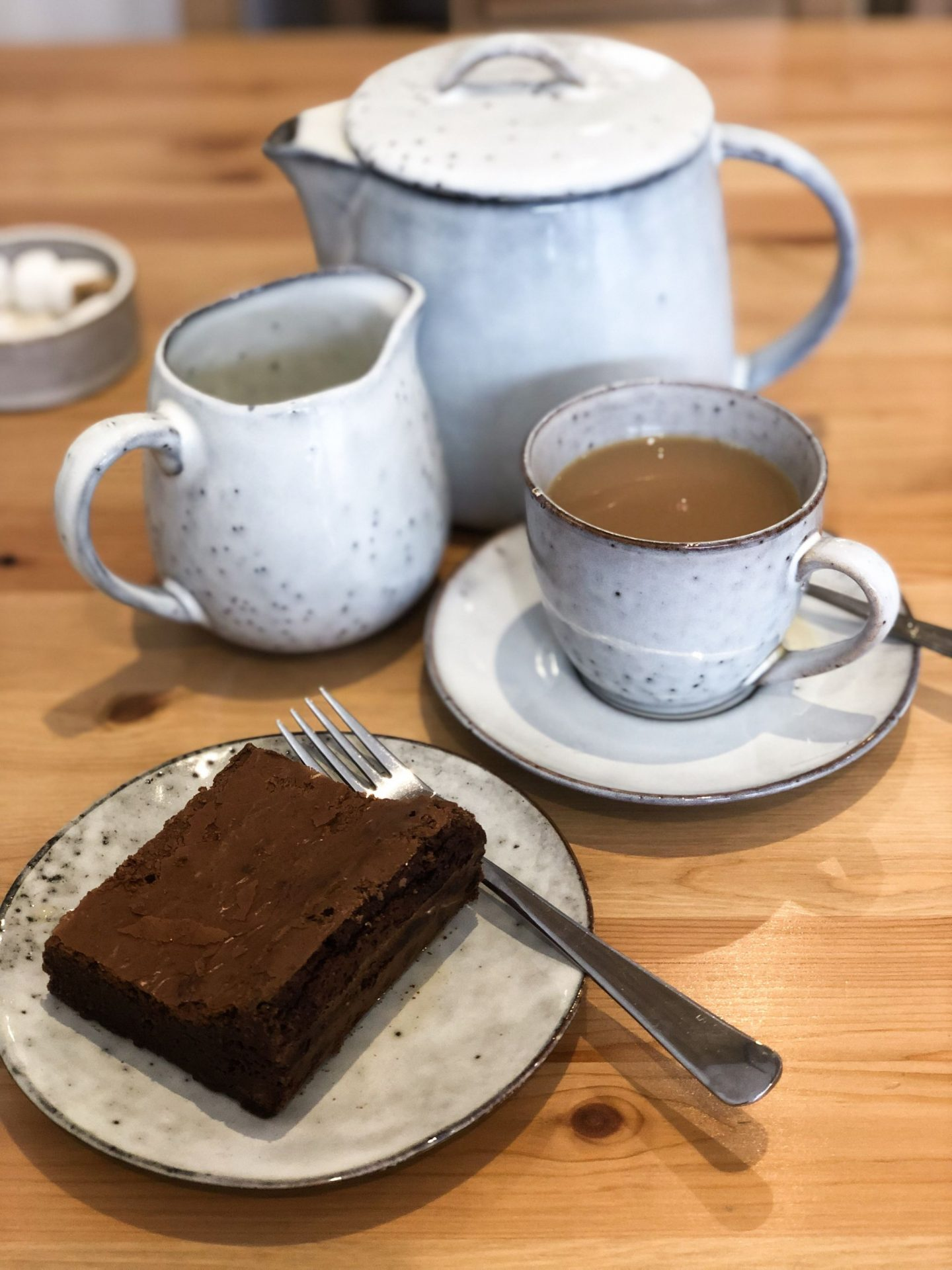 A rich, gooey chocolate brownie sat on a mottled grey plate with a fork, ready to be eaten. In the background is a cup of tea, a teapot and a jug of milk. This is at Workshop, one of the best cafes in Leeds.