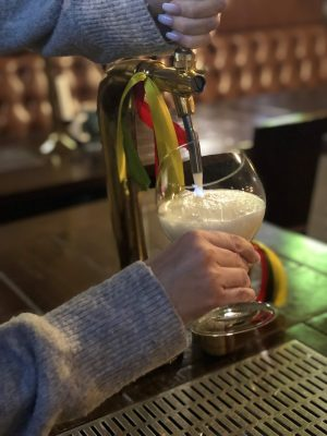 vilnius bars: two hands pulling a beer at a pour-your-own-beer bar