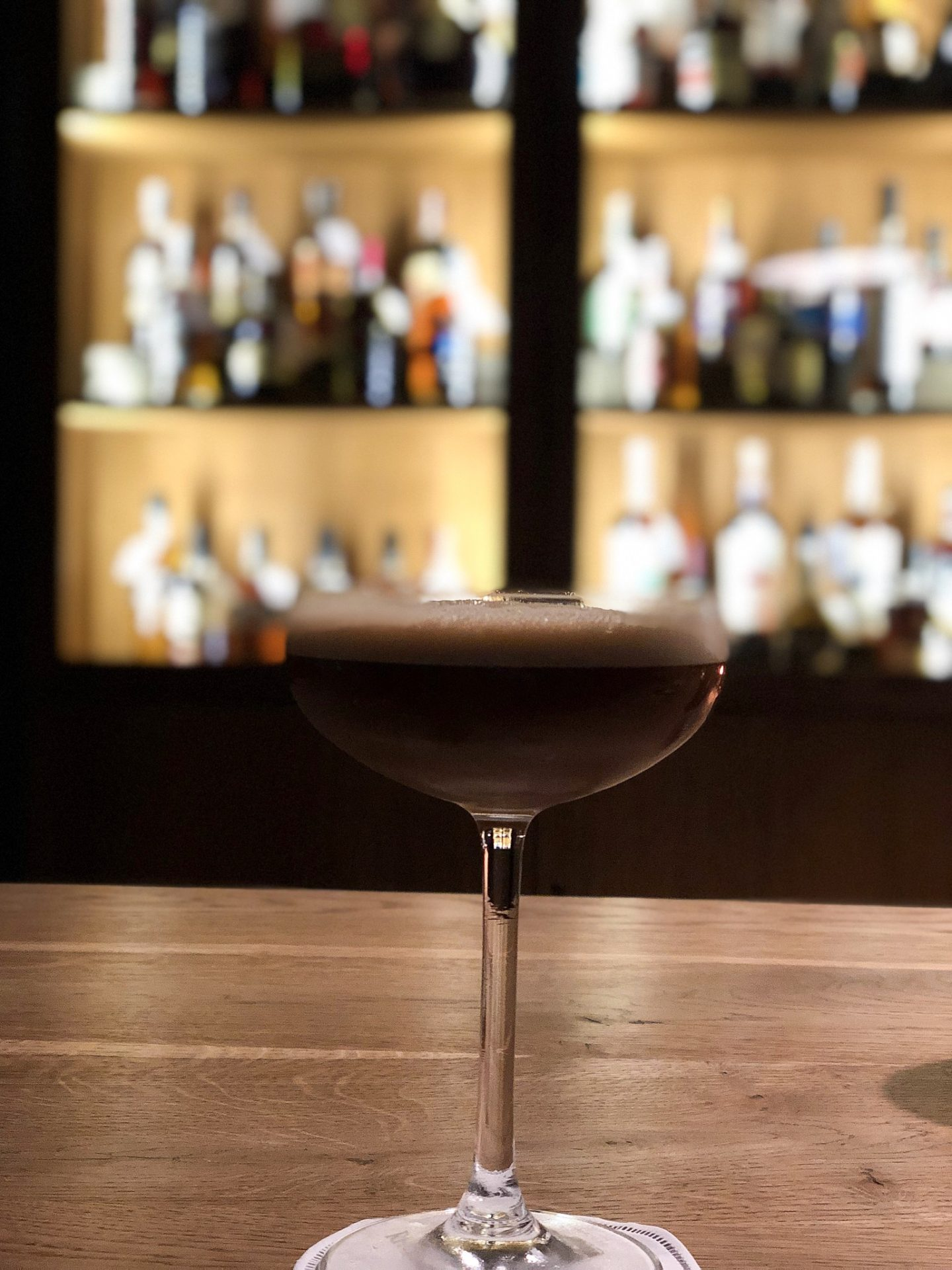 vilnius bars: espresso martini on a wooden table in a low lit bar
