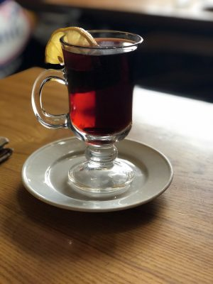 vilnius bars - a cup of mulled wine with a lemon hanging off the rim