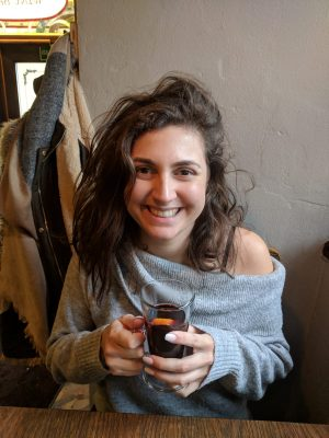 vilnius bars: Nell with very messy hair holding a glass of mulled wine and smiling at the camera