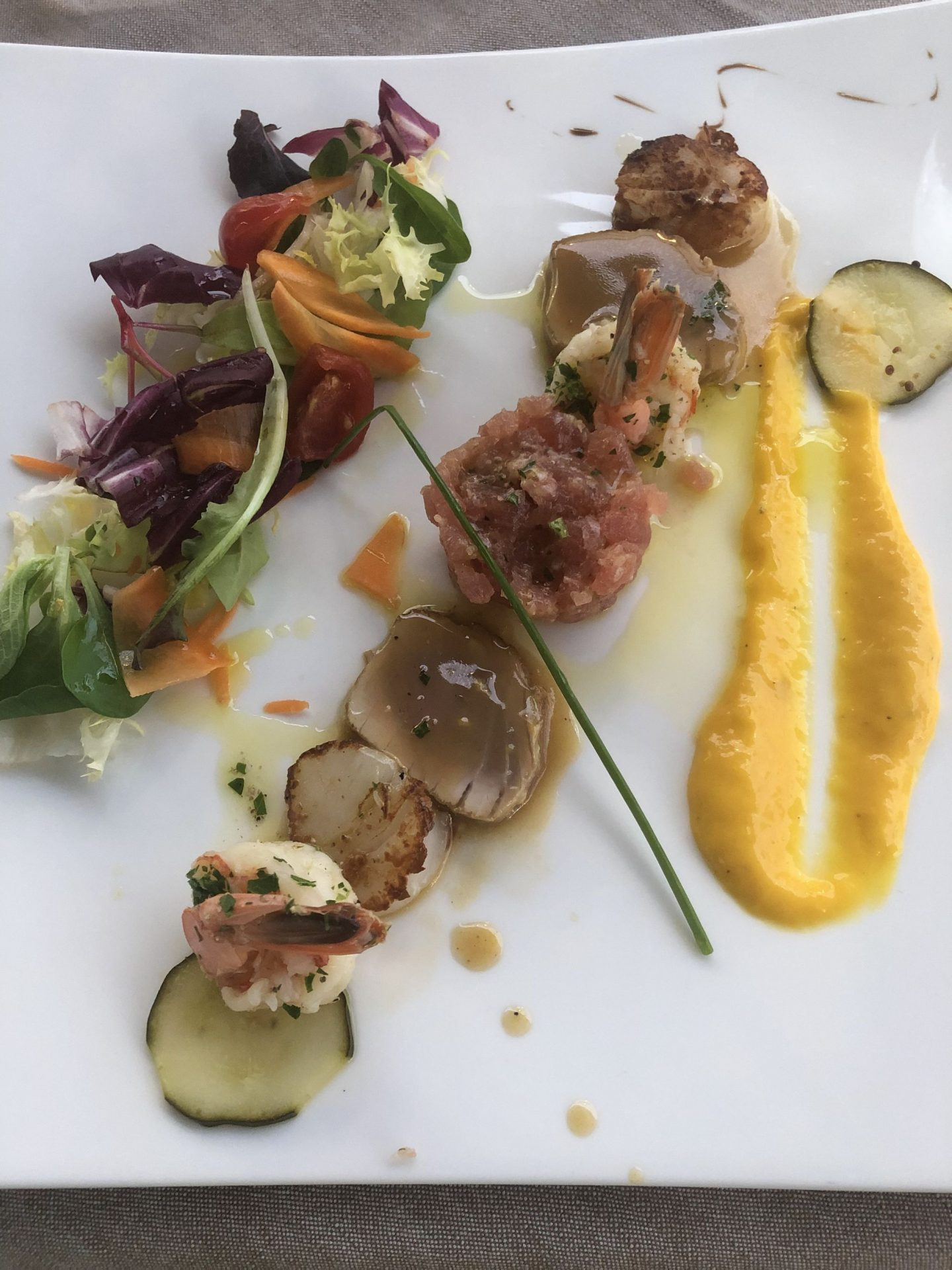 overhead shot of seafood composition with brightly coloured mango puree in Trento, Trentino