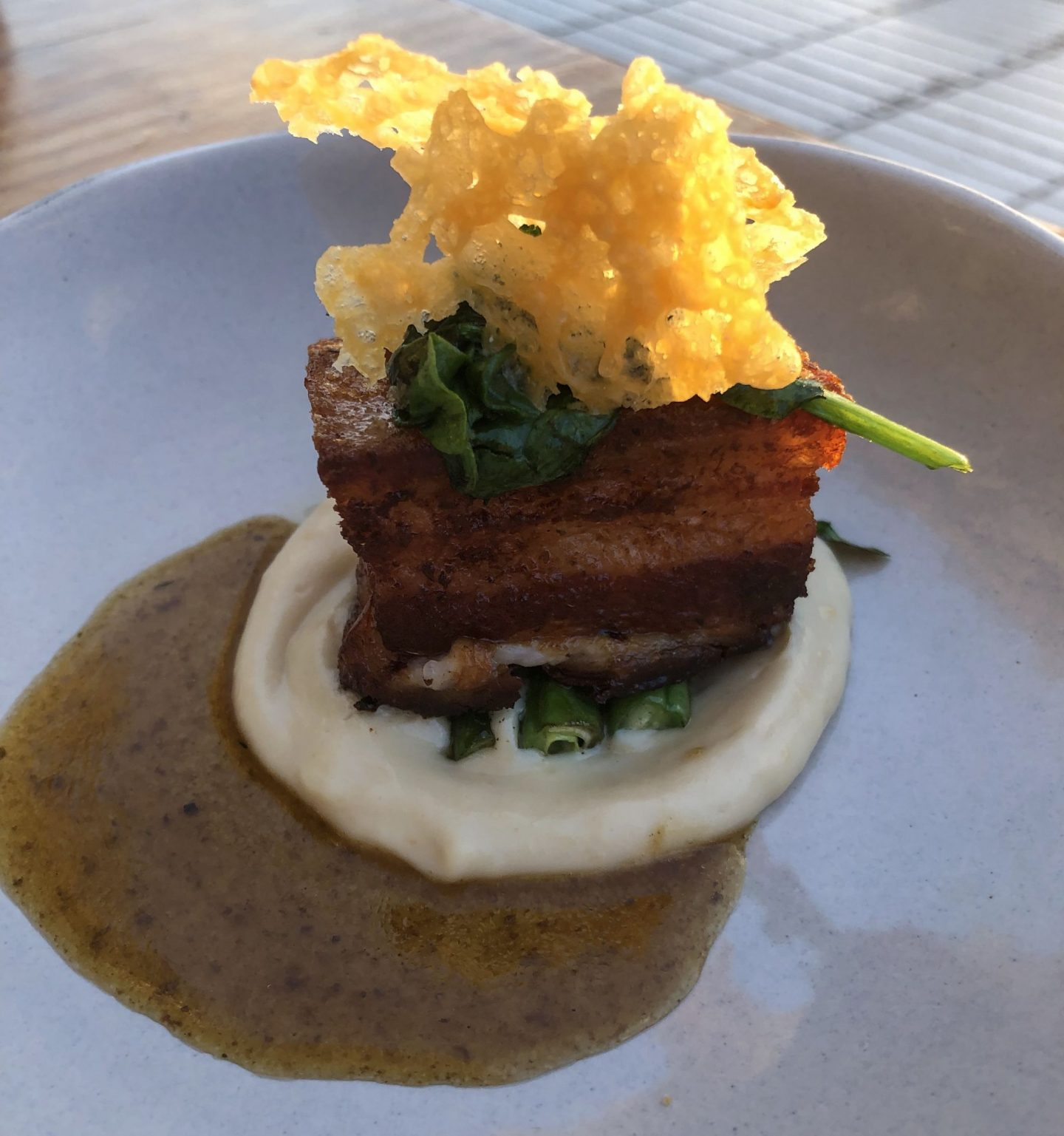 Pork belly on cauliflower puree topped with a parmesan crisp, sat on a white plate in Gran Canaria