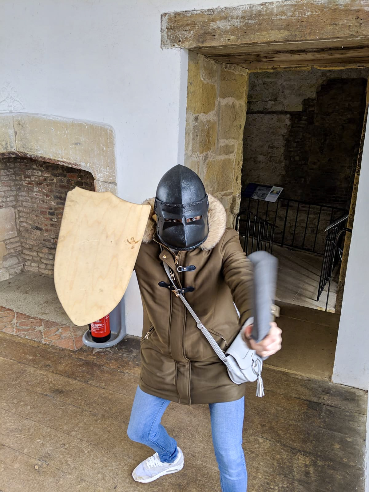 Nell dressed in a plastic helmet, holding a plastic sword and wooden shield, in Helmlsey Castle - things to do Helmsely